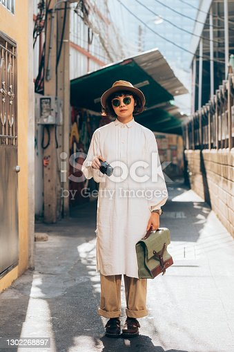 A beautiful Asian woman standing in the street with a camera in her hand.