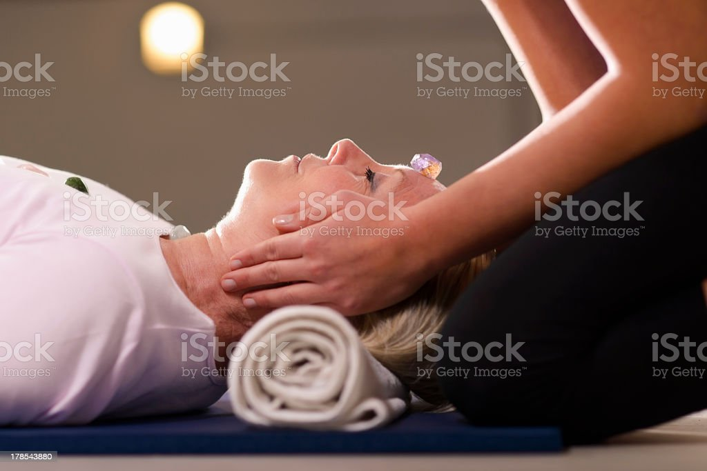 Young therapist arranging crystals on female client for reiki th stock photo
