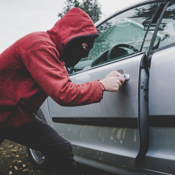 young thief managed to break the car door using sceleton key. evil-doer in black mask and hoodie unlocked the vehicle and got access to car cabin. drug addict with hidden face hacks the automobile - going inside eye imagens e fotografias de stock