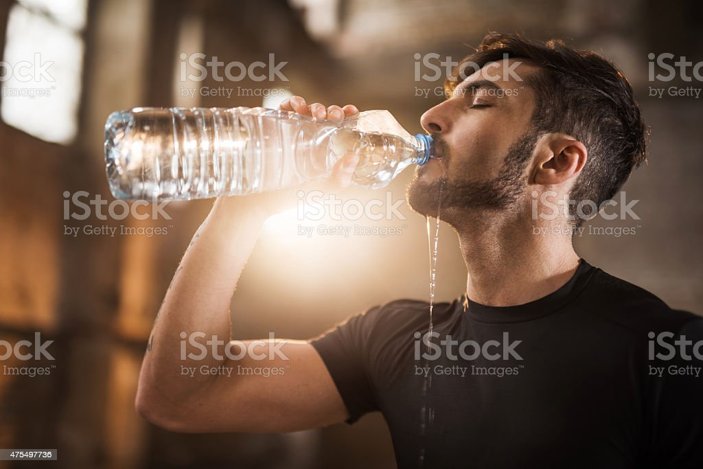 Young thirsty athlete drinking water after exercising. stock photo