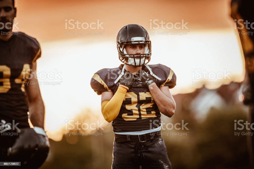 Young thoughtful American football player on the field at sunset. royalty-free stock photo