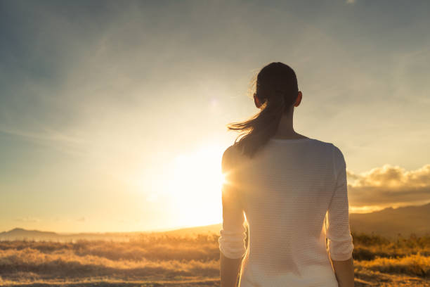 Young thoughtful female facing beautiful sunset. stock photo