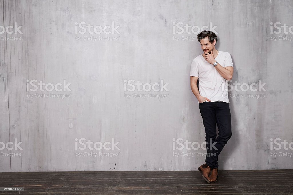 Young thoughtful man against wall stock photo