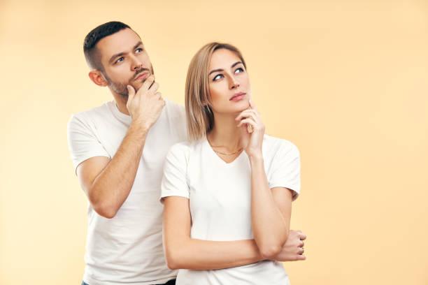 Joven hombre y mujer reflexivo mirando hacia los lados aislados sobre fondo beige - foto de stock