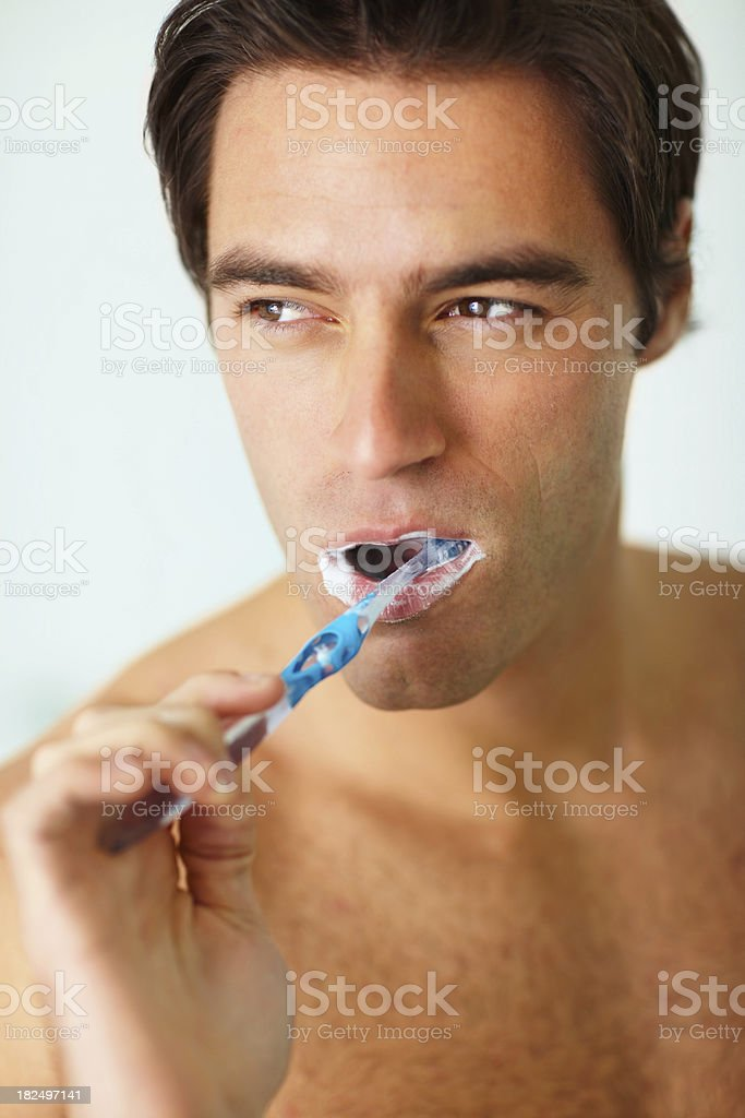 Young thoughtful man brushing his teeth royalty-free stock photo