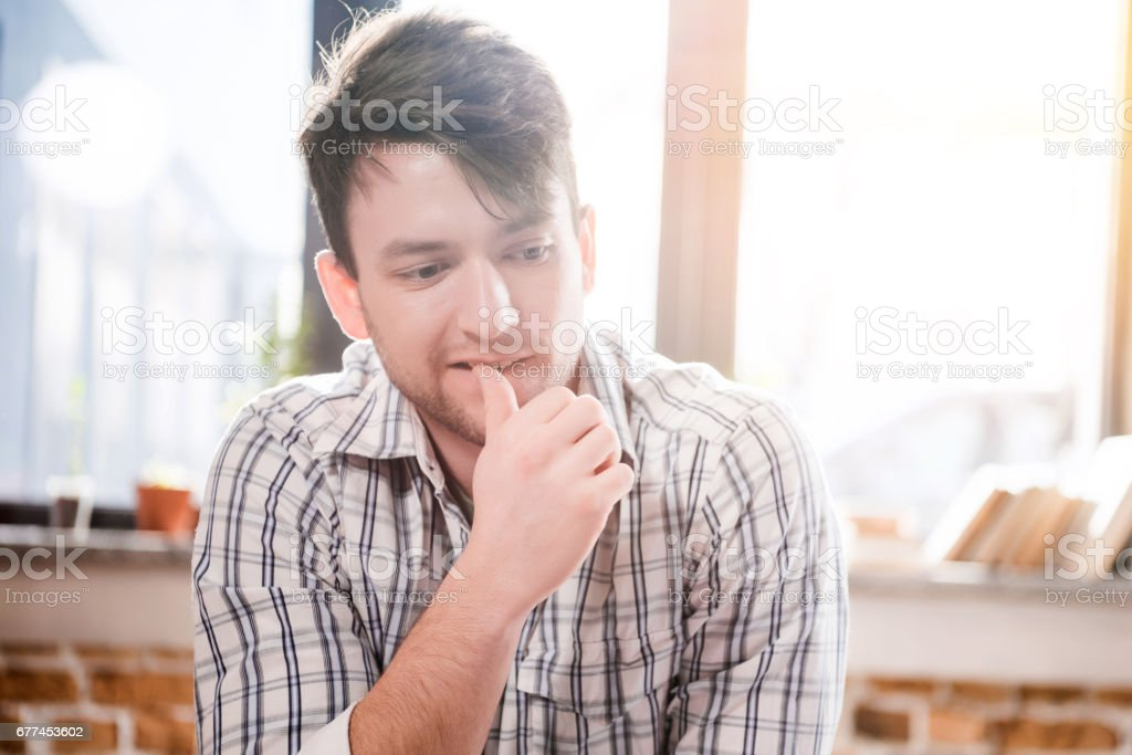Young thoughtful man owner of small business sitting with hand on chin and looking away stock photo