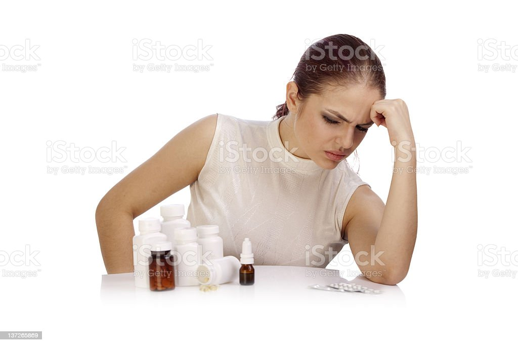 Young thoughtful woman looking at a group of pill bottles. royalty-free stock photo