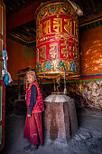 A young Tibetan Buddhist monk turning the prayer wheels, Lo Manthang in Upper Mustang. Mustang region is the former Kingdom of Lo and now part of Nepal,  in the north-central part of that country, bordering the People's Republic of China on the Tibetan plateau between the Nepalese provinces of Dolpo and Manang.