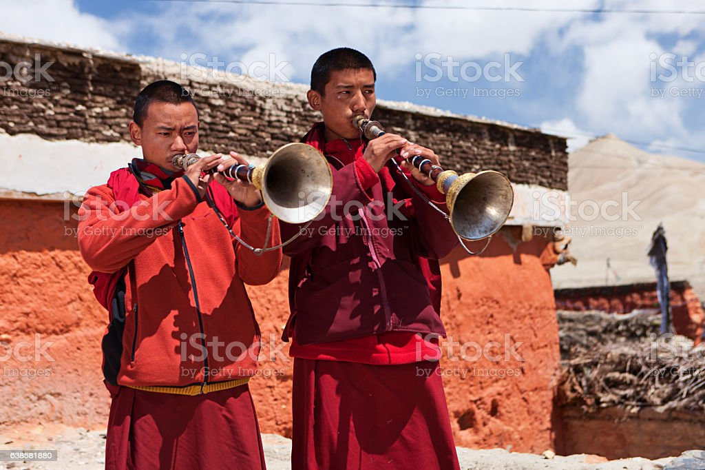 Young Tibetan monks playing buddhist horns on the roof, LoManthang stock photo