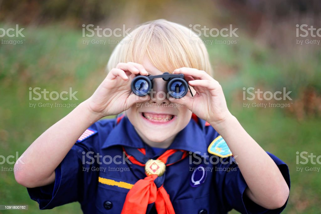 Young Tiger Cub Scout Smiling at Camera Through Binoculars stock photo