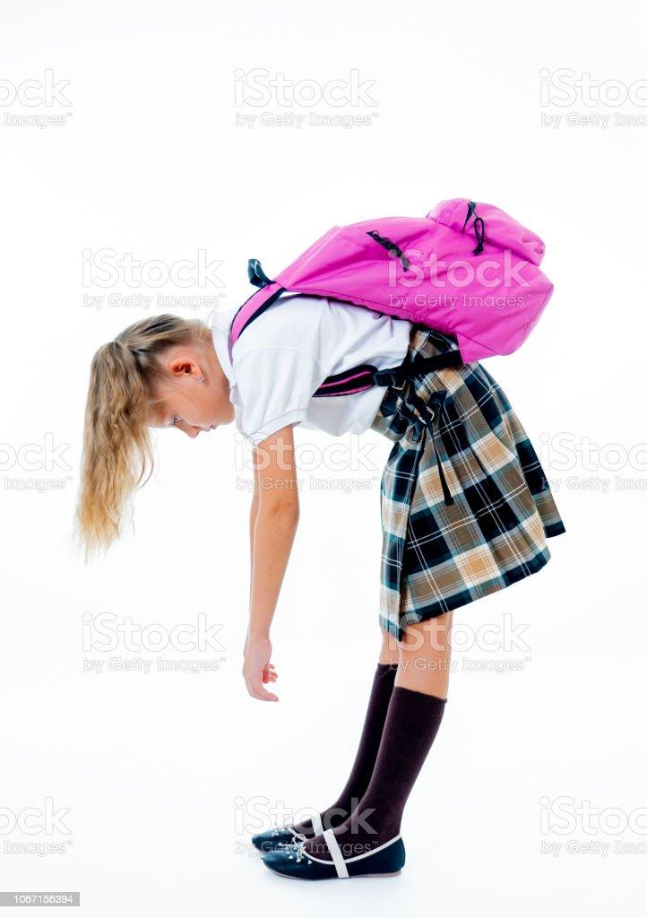 Escola jovens cansados e tristes bonito menina em pé com um saco grande de escola de costas sobre um fundo branco isolado por uma volta dor stress lição de casa e volta ao conceito de escola. - foto de acervo