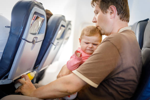 Young tired father and his crying baby daughter during flight on airplane going on vacations stock photo