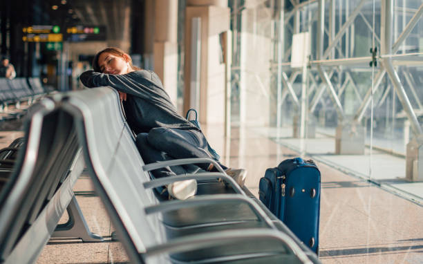 Young tired woman sleeping alone in empty airport with her hand luggage, waiting flight - transportation, low cost traveling, delayed or cancelled flight concept Young tired woman sleeping alone in empty airport with her hand luggage, waiting flight - transportation, low cost traveling, delayed or cancelled flight concept jet lag stock pictures, royalty-free photos & images