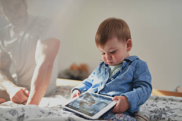 Young toddler child playing game on digital tablet wearing jean shirt sitting on bed stock photo