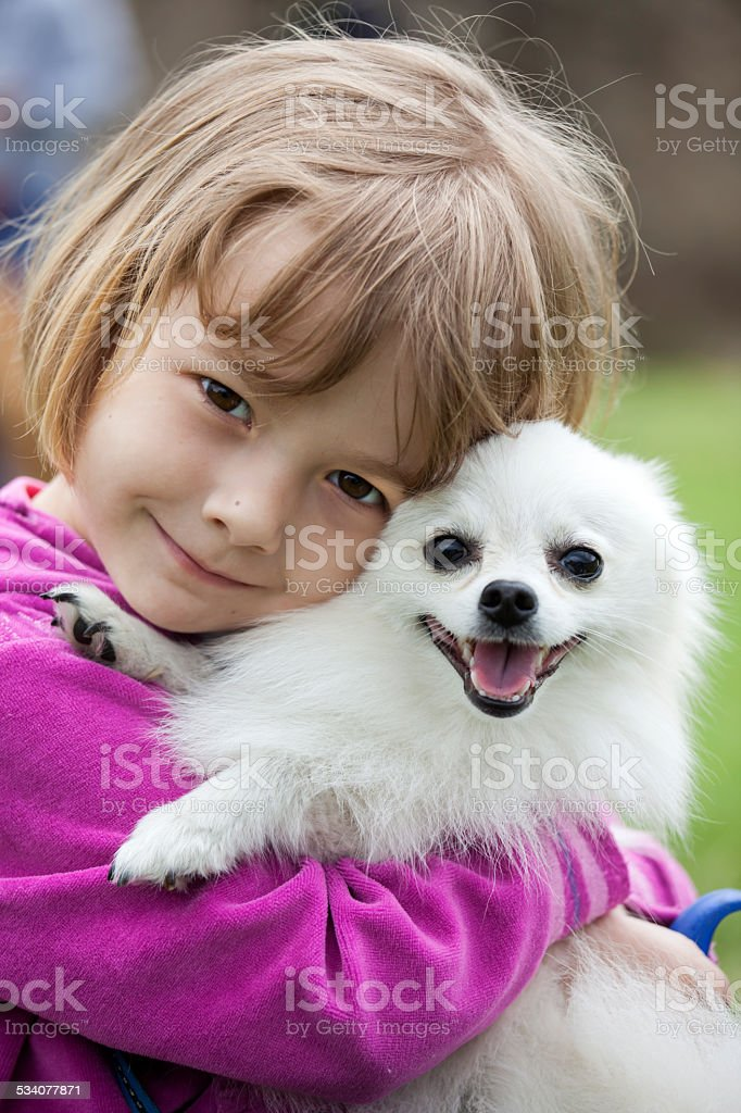young toddler cuddling her pet dog stock photo