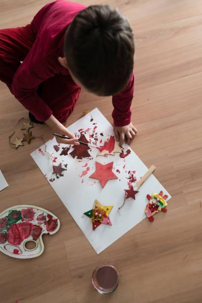 junge kleinkind weihnachten dekorationen auf dem boden kniend - weihnachtsbilder zum ausmalen stock-fotos und bilder