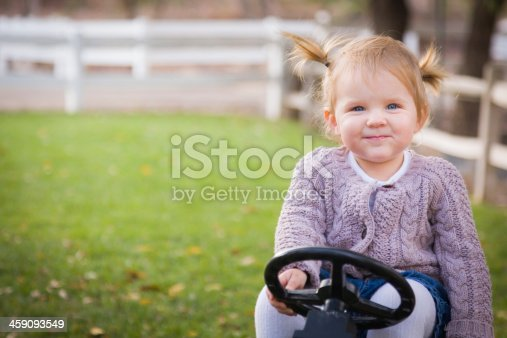 Happy Young Toddler Smiling and Playing on Toy Tractor Outside.
