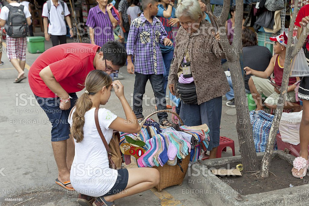 Young tourist couple buying socks from senior Thai woman. royalty-free stock photo