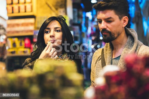 Young tourist couple eat Turkish Delight  in Grand Bazaar, Istanbul, Turkey