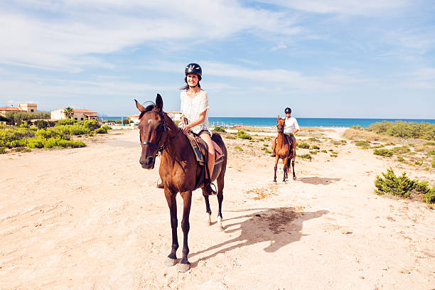 young tourist couple horseback riding stock photo