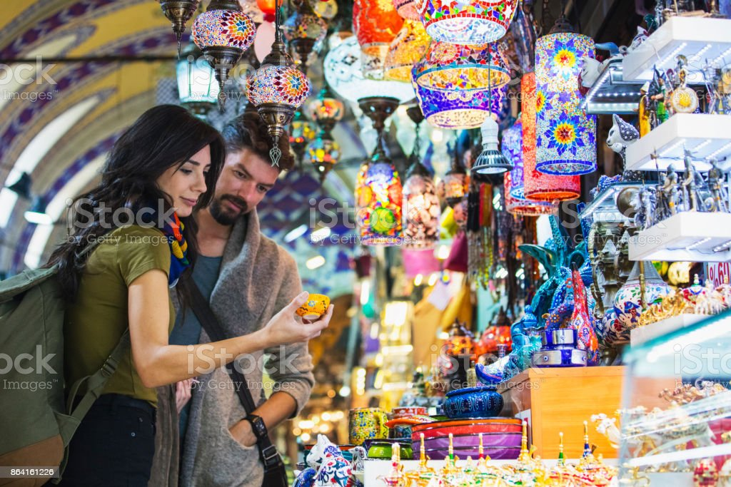 Young tourist couple shopping in in Grand Bazaar, Istanbul, Turkey - Foto stock royalty-free di 2017