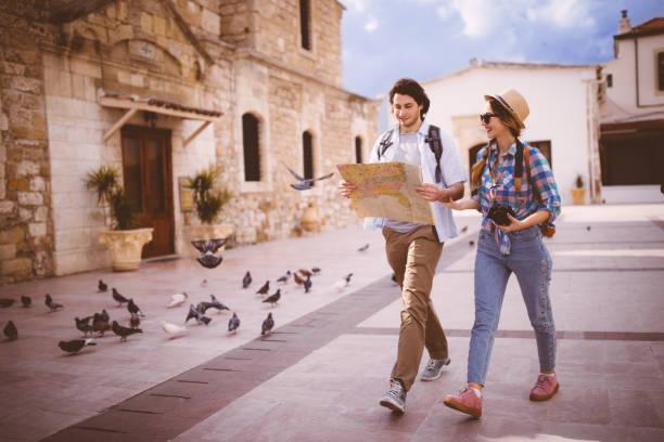 junge touristen paar herum mit karte im mediterranen ambiente - hochzeitsreise zypern stock-fotos und bilder