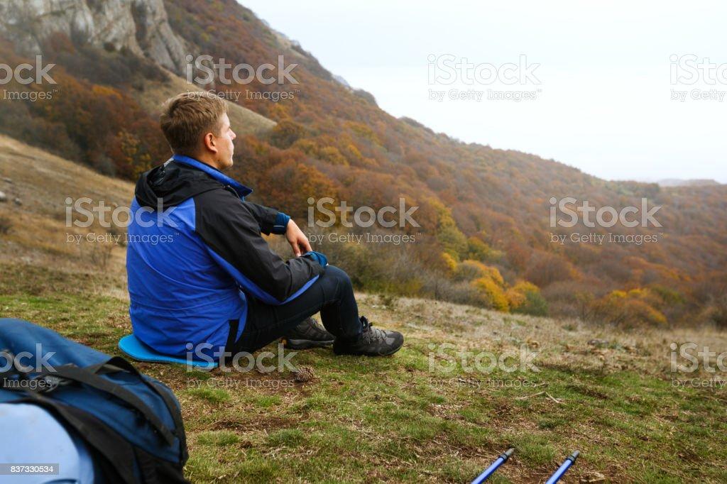 Alpinista do jovem turista com mochila, localização e relaxante no topo da colina em montanhas e olhar lindo amarelo outono paisagem por do sol paisagem - foto de acervo