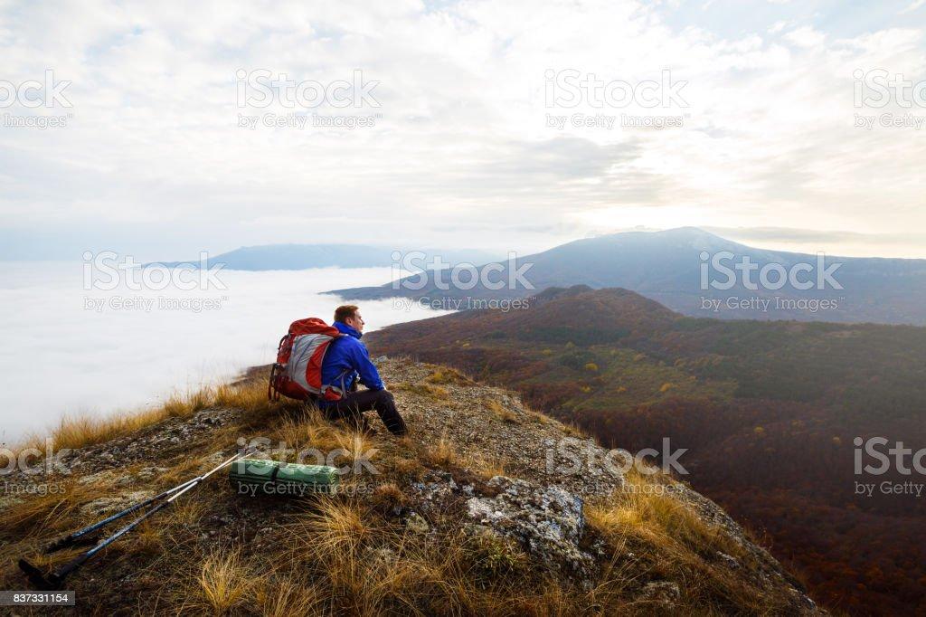 Alpinista do jovem turista com mochila, localização e relaxante no topo da montanha e olhar amarelo outono paisagem pôr do sol sobre as nuvens - foto de acervo