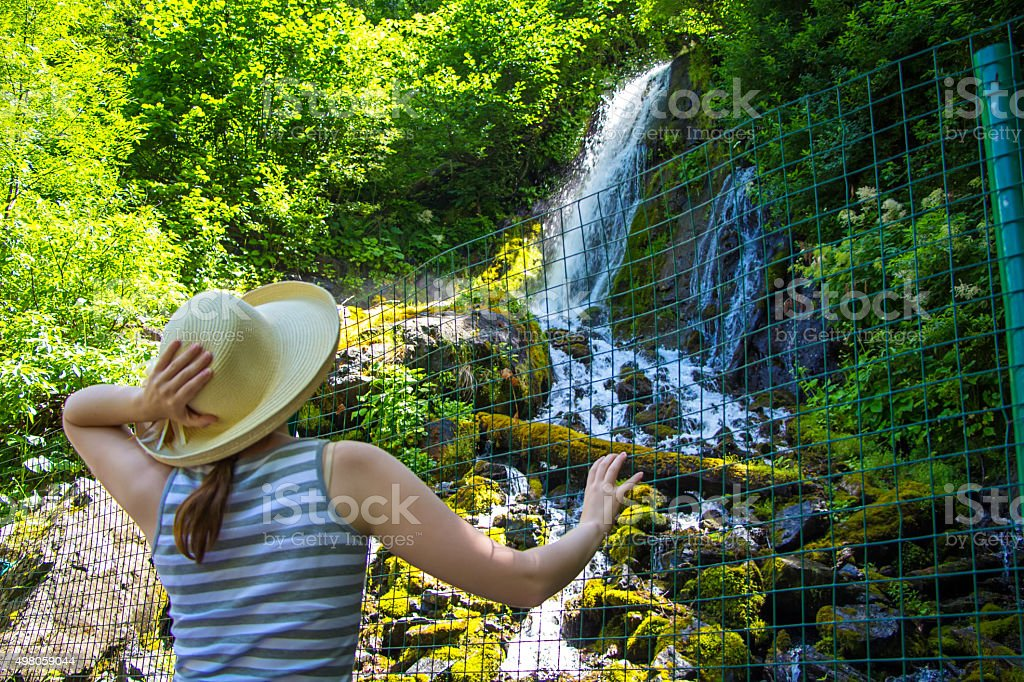 Young tourist looking at waterfall stock photo