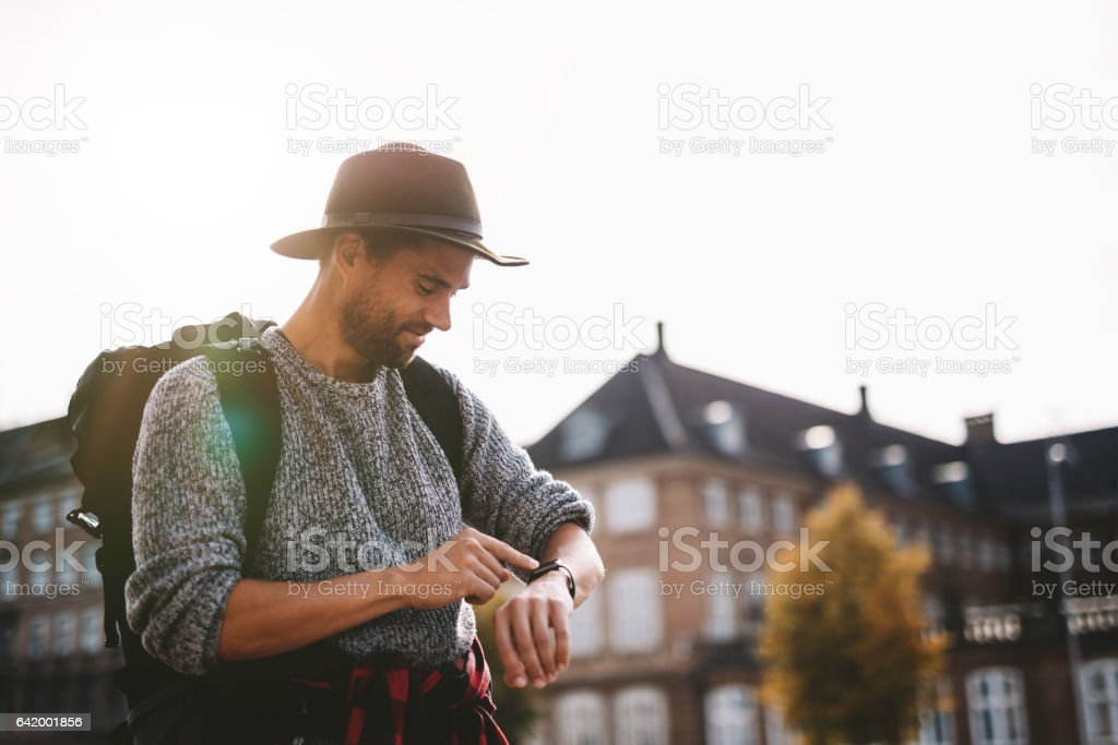 Young tourist looking at wrist watch. stock photo