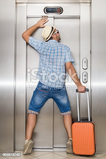 638591126istockphoto Young tourist man can not get out of the elevator 905878240