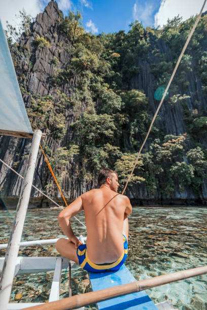 A young tourist man from a rare view sitting on a boat looks at the cliffs in Coron, Philippines stock photo