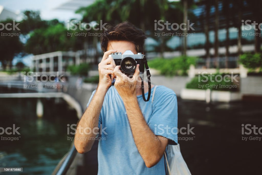 Young Tourist Man In Singapore Taking Phots With A Retro Styled Camera Stock Photo Download Image Now Istock See more ideas about poses, photoshoot, photography poses. young tourist man in singapore taking phots with a retro styled camera stock photo download image now istock