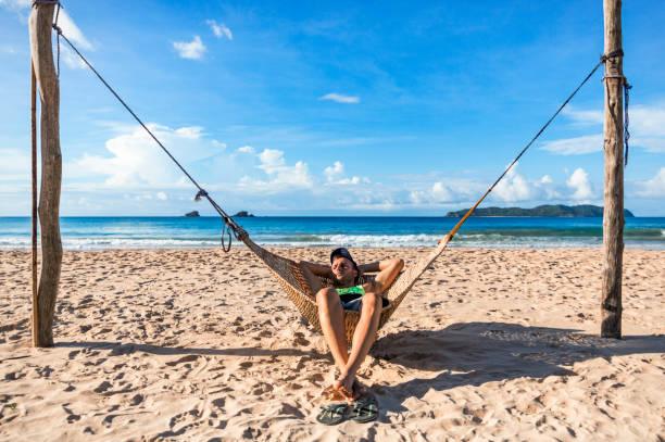 A young tourist man lies on a hammock in Nacpan beach, near El Nido, Palawan, Philippines stock photo