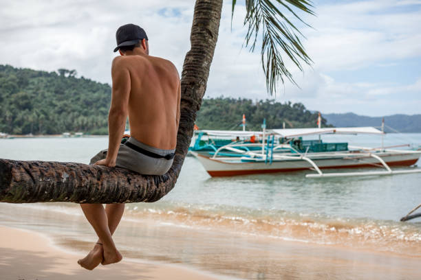 A young tourist man sitting on a bent palm tree next to the beach in Port Barton, Palawan, Philippines (rare view) stock photo