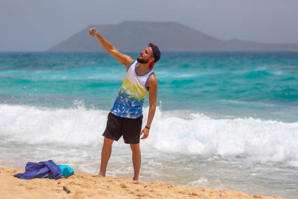A young tourist man taking a selfie with the phone next to the beach in Fuerteventura, Spain stock photo