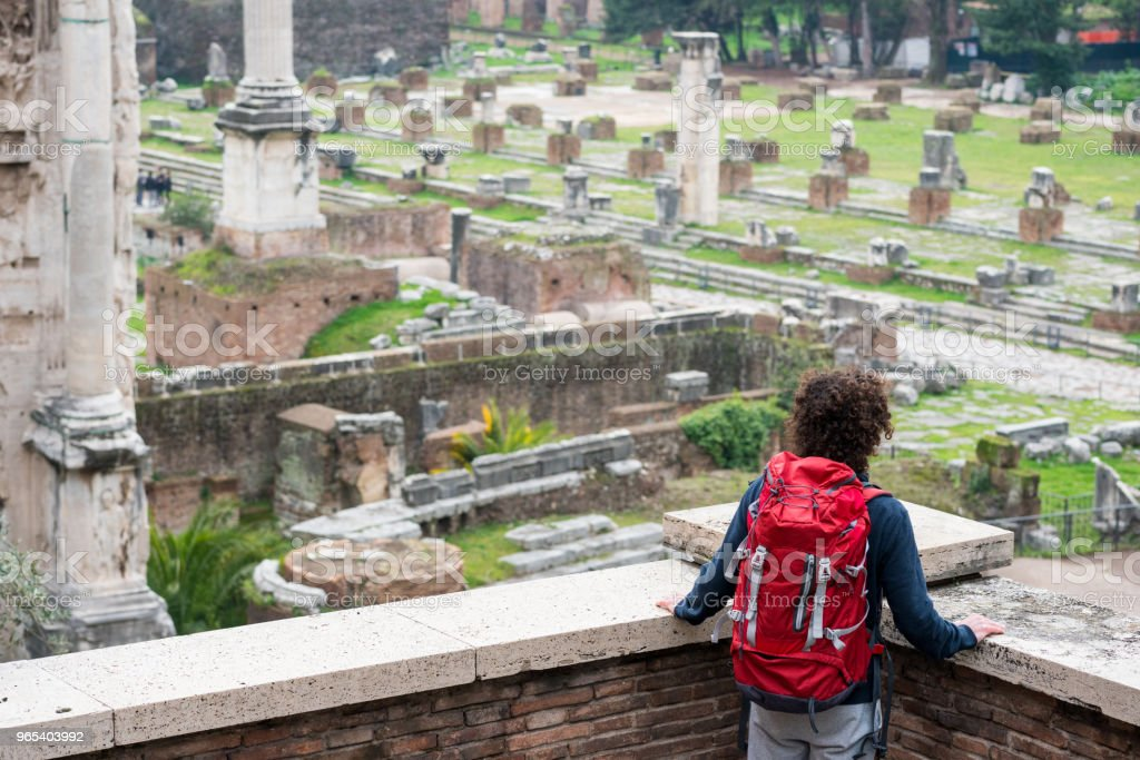 Young tourist man with red backpack looking at Roman forum royalty-free stock photo