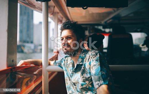 Young tourist moving around Bangkok, using a ferry boat. He is wearing a summertime fashion Hawaiian shirt, watching the Bangkok panorama around him.