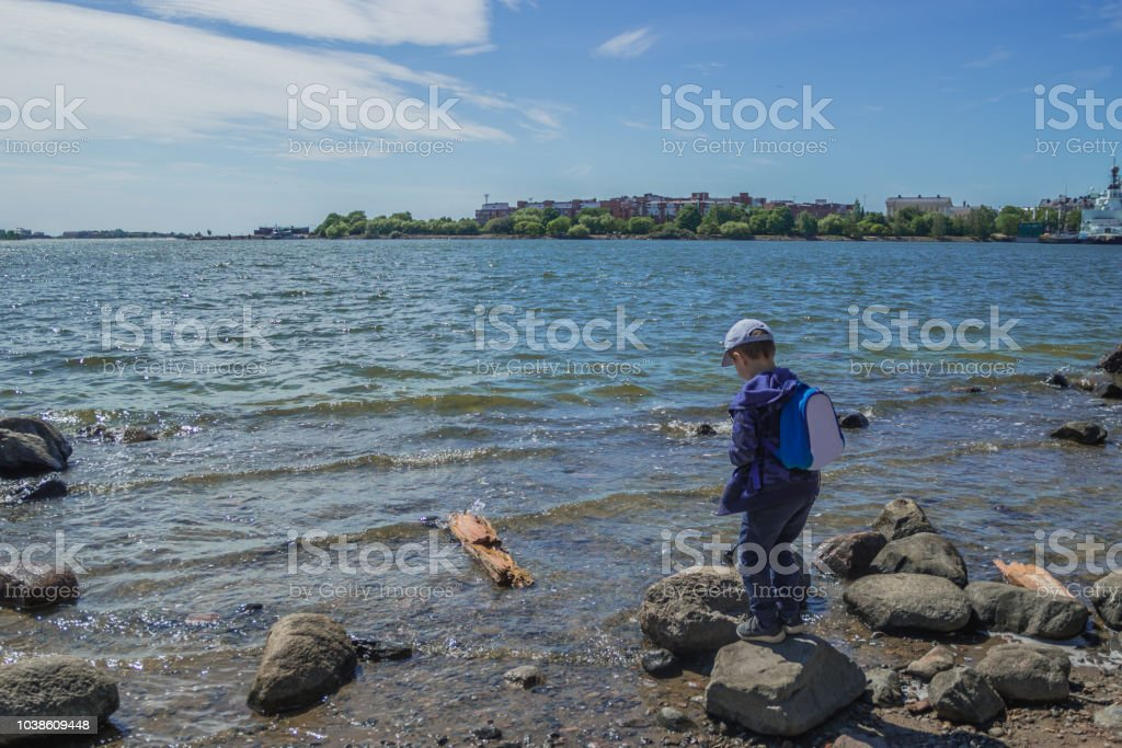 Young tourist standing near water adn looking at it. Travel and adventure concept. Vacations. stock photo