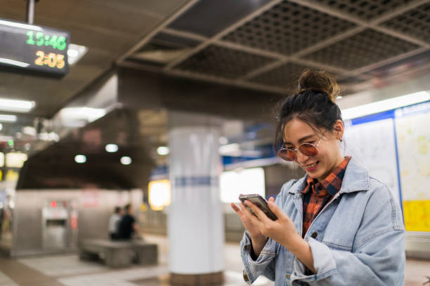 Young tourist using phone on subway station stock photo