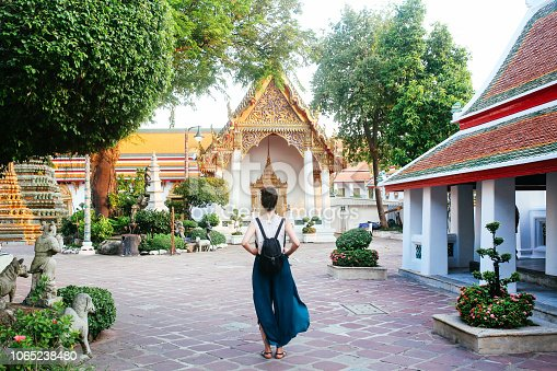 Young tourist woman enjoying her day in the famous Wat Pho Buddhist temple in Bangkok, Thailand. She is walking on a nice, sunny day, contemplating, enjoying the rich history of the famous place.