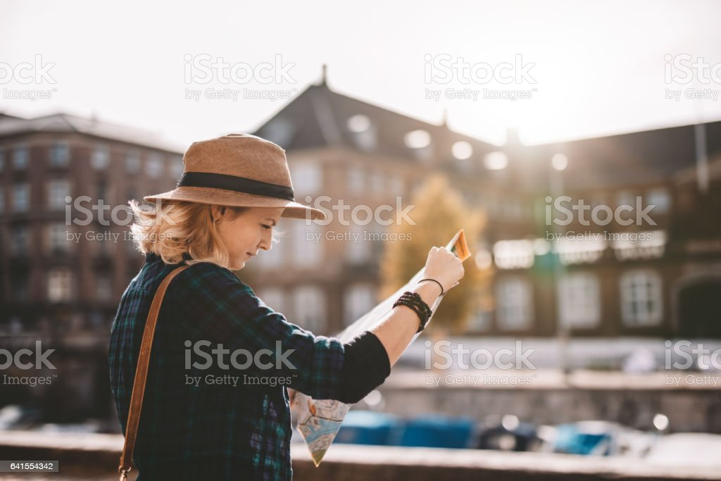 Young tourist woman looking at a navigation map. stock photo