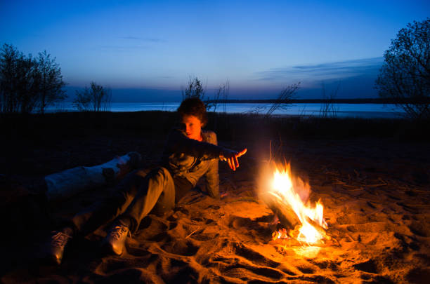 young tourist woman pulls her hand to the night fire on the beach stock photo