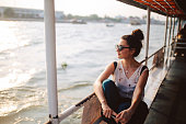 Young tourist woman moving around Bangkok, using a ferry boat. She is wearing sunglasses, watching the Bangkok panorama around her.