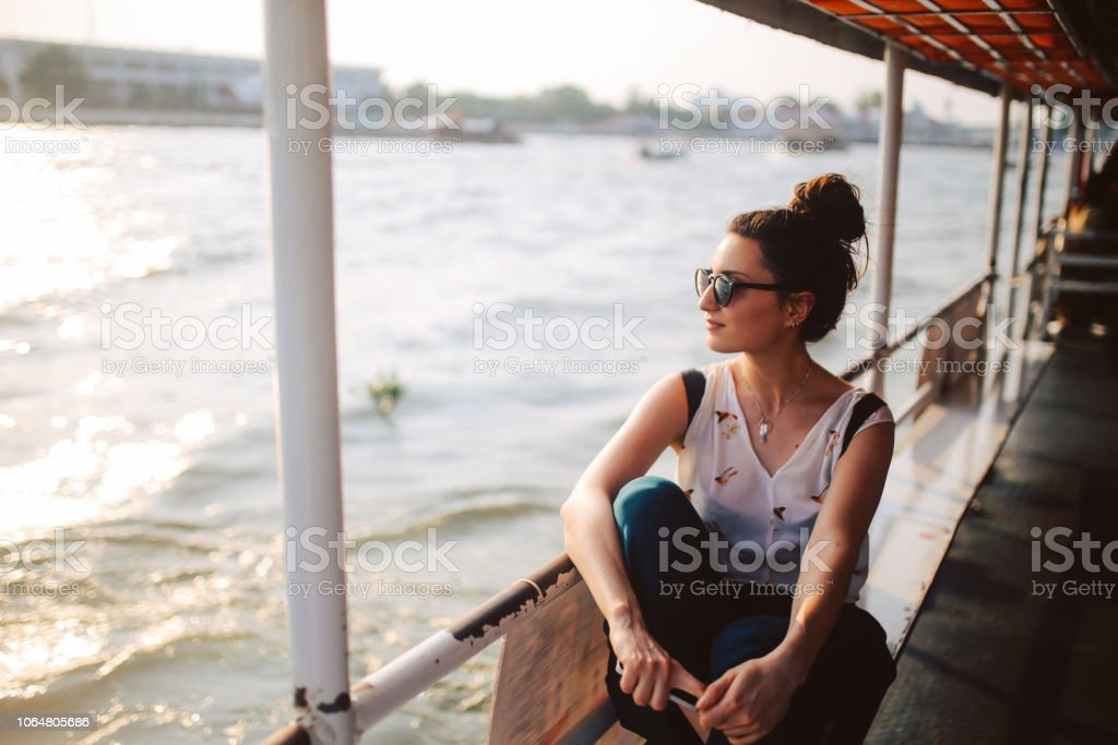 Young tourist woman riding on the Bangkok ferry boat stock photo