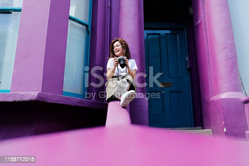 Young tourist woman sitting on the color walls