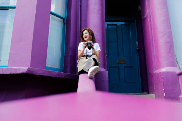 Young tourist woman sitting on the color walls stock photo