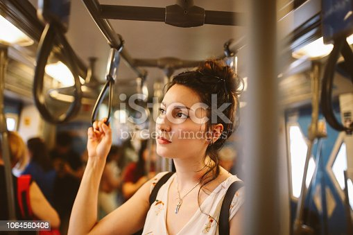 Young tourist woman moving around Bangkok, using public transport. She is tired, standing in the subway wagon, waiting for her station.