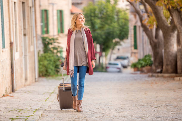 Young tourist woman walking with suitcase stock photo