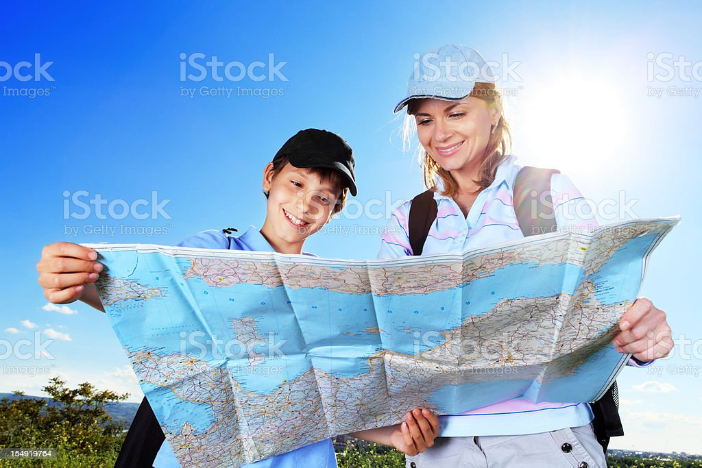 Young tourists are looking at the map. stock photo